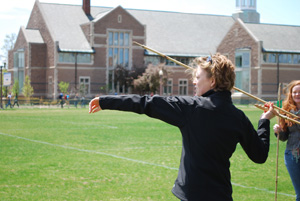 Student throwing atlatl at Anthropology Spring Party
