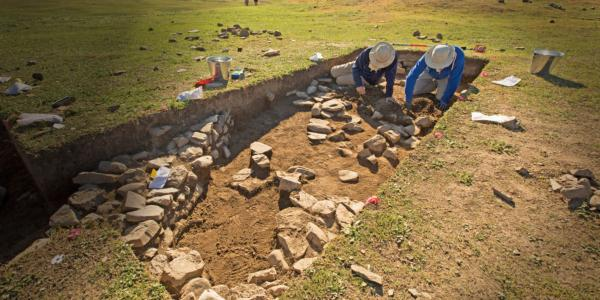 Two people kneel in an excavation site surrounded by stones and tools